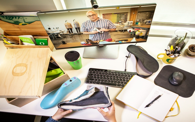 Student desk with materials and shoemaking kit and a computer screen showing image of SPM instructor teaching an online course