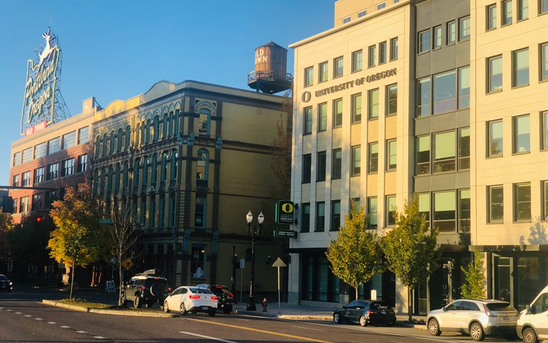 Photo of the UO Lundquist College of Business location in Portland in early morning with the sun rising and lighting up the building with the UO White Stag block in the background