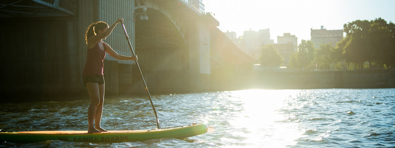 SPM student on a standup paddle board on the Willamette River under one of Portland's iconic bridges