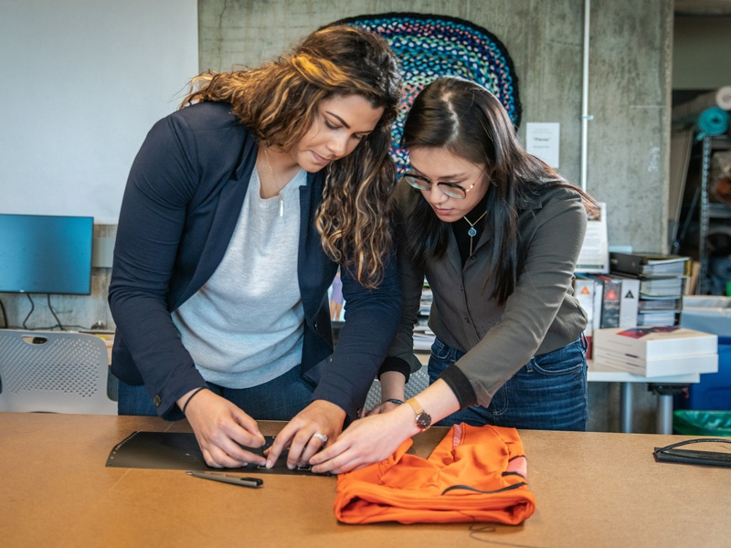 Two female SPM students work on designing an outdoor apparel garment