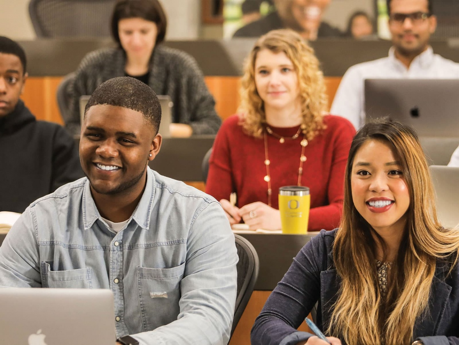 Sports Product Management students in class facing the camera and smiling in response to a professors point