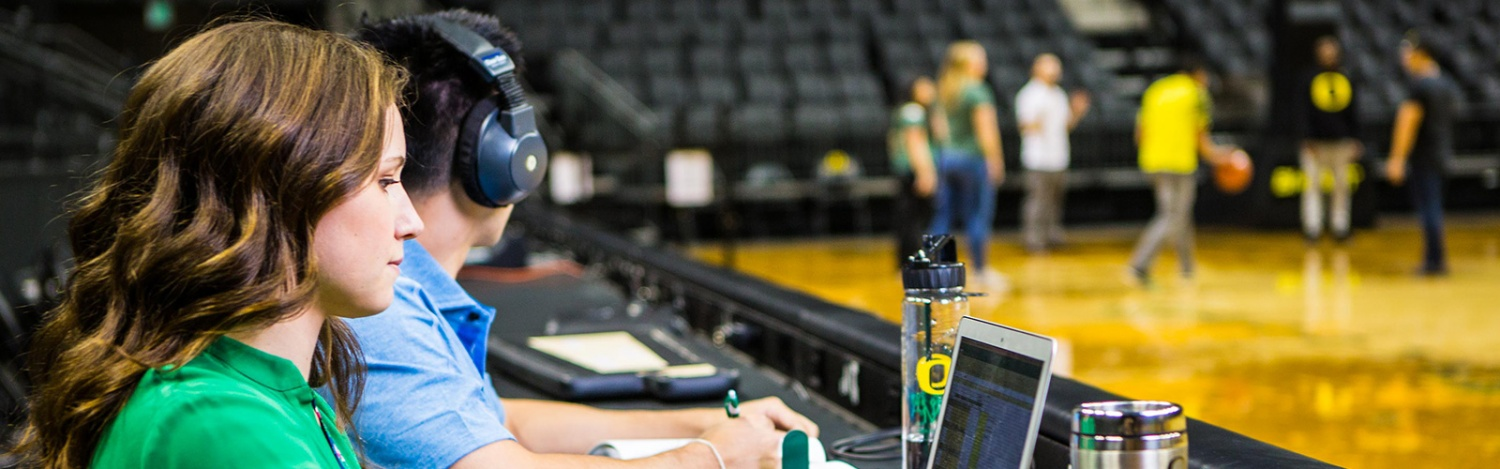 Students manage operations on the floor of a sports arena