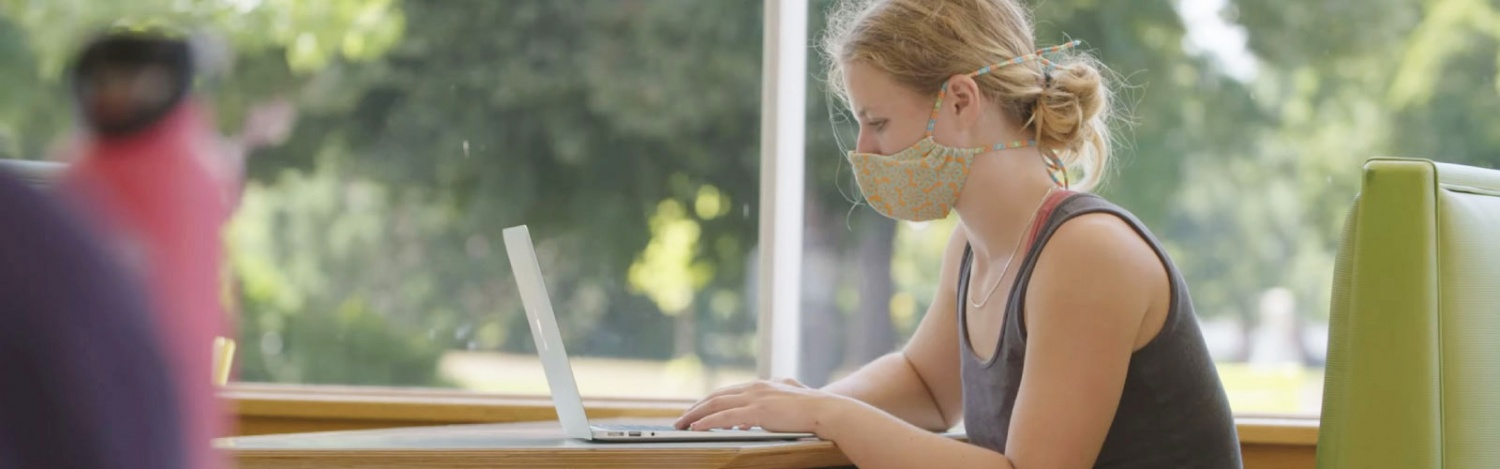 A student wearing a mask works on a laptop