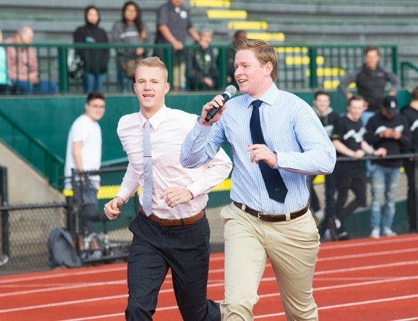 Two students pitch a business plan while running on Hayward Field