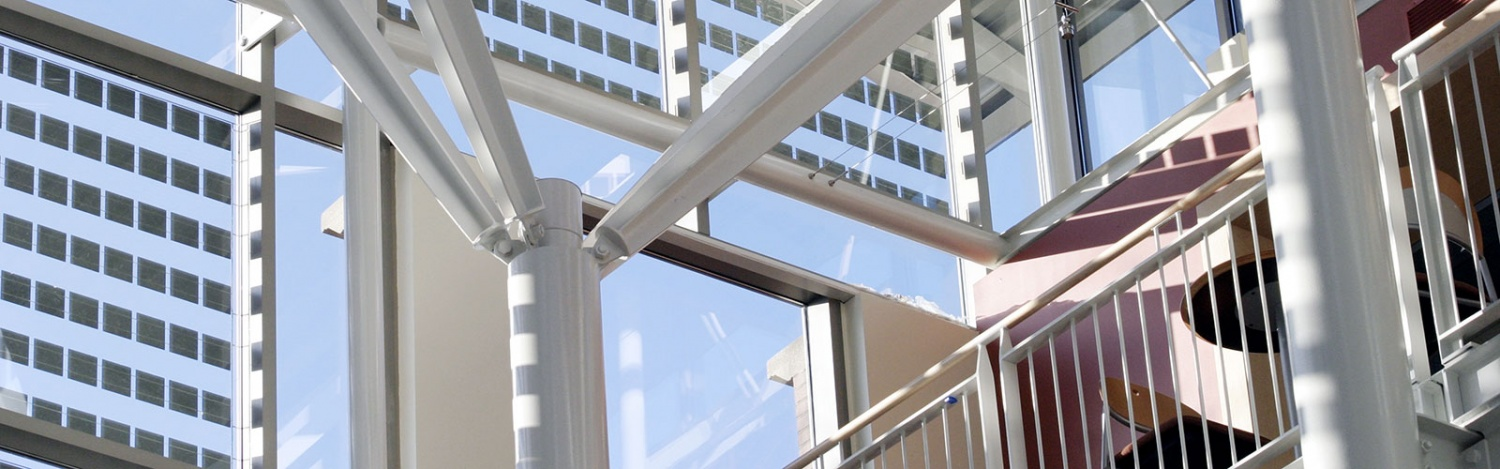 Close up artistic photo of a small portion of the Lillis Business Complex roof and south windows taken from inside with blue sky and sun shining and photovoltaic solar cell squares embedded in the glass of the windows