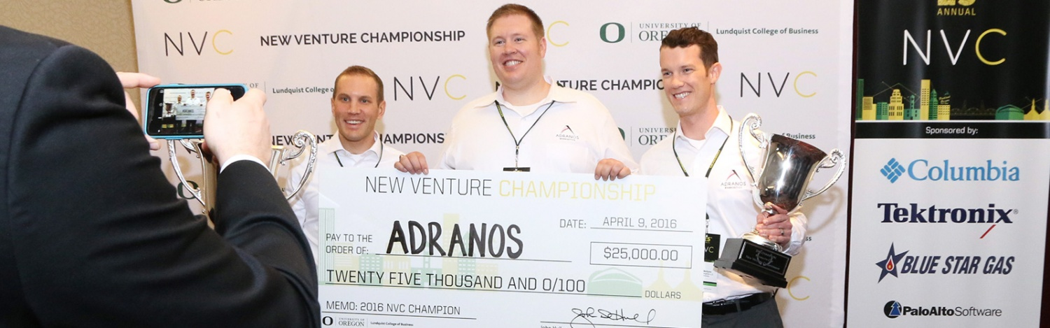 The Adranos team holds up their first place check
