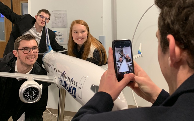 Three OCG members take a photo next to a model of an Alaska Airlines plane