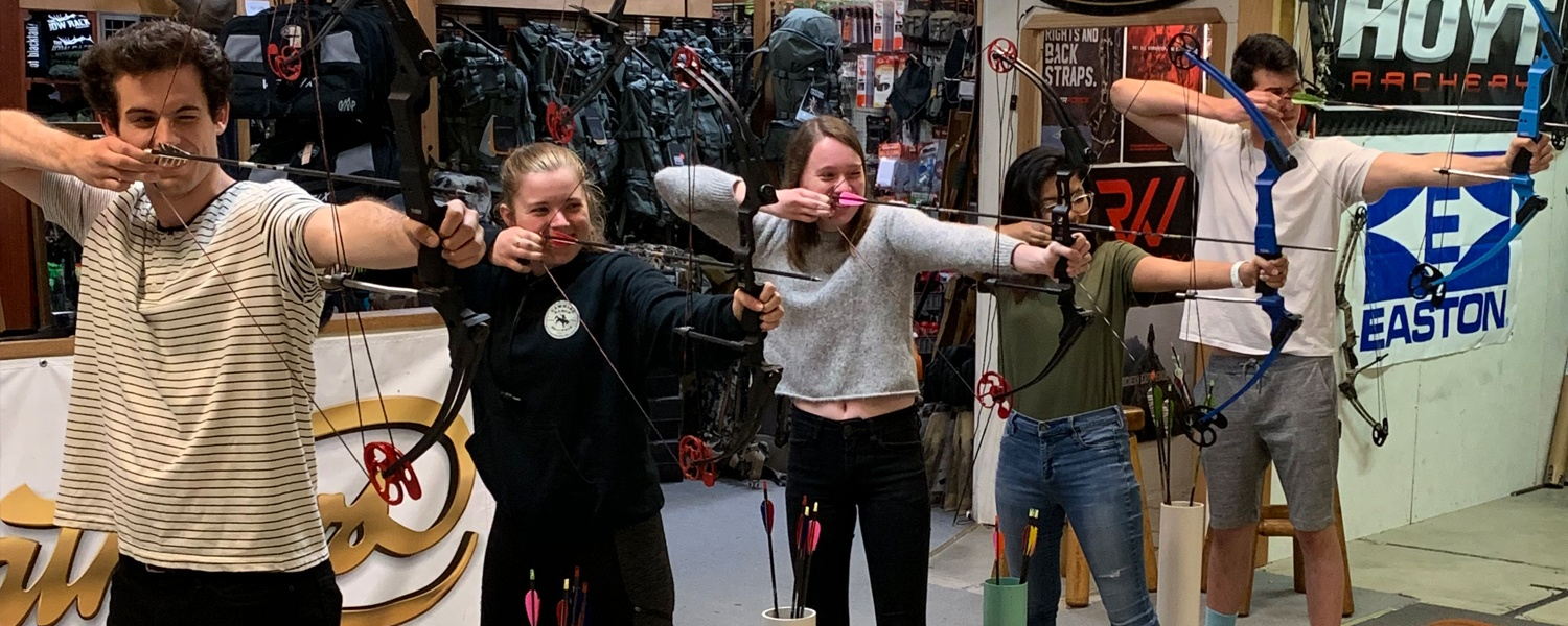 OCG members test out archery equipment in an outdoor store
