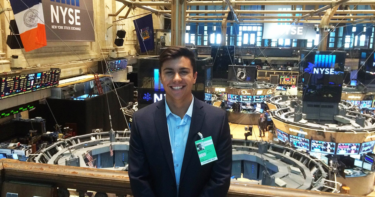 A student stands above the New York Stock Exchange