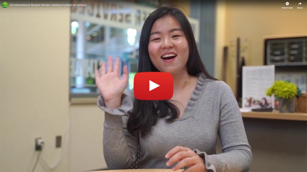 Screencap of a YouTube video. An international student is waving a the camera.