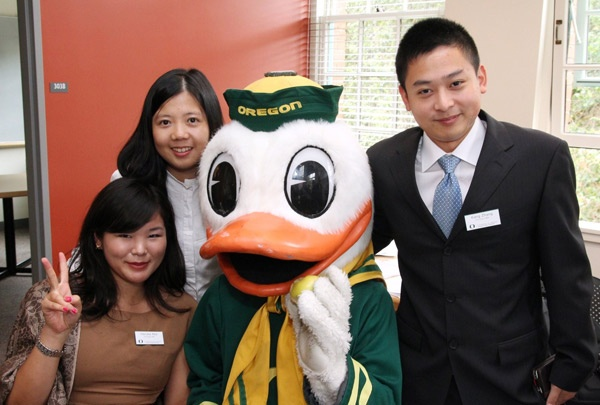 MBA students pose for a photo with the Duck