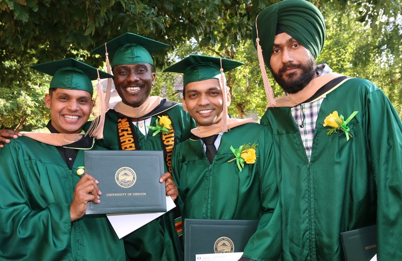 Four graduates in commencement robes pose for a group photo