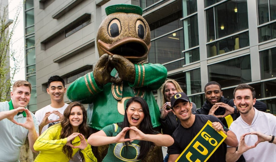 A group of students throw the O in front of the Duck statue