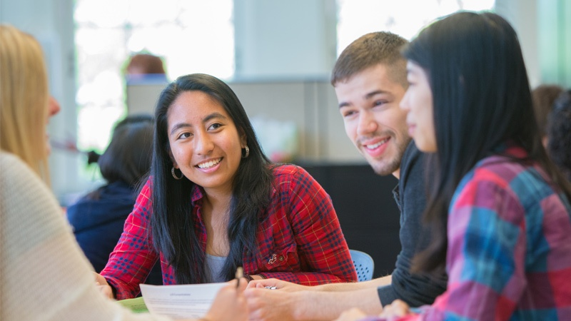 Four students discuss coursework in the advising office