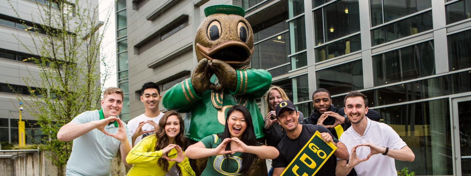 Students throw the O in front of a bronze statue of the Duck