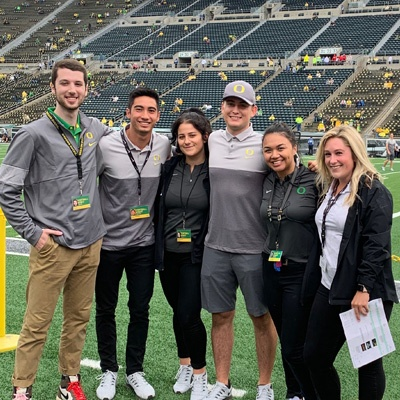 A group of Warsaw Sports Business Club members pose for a group photo on the field at Autzen Stadium