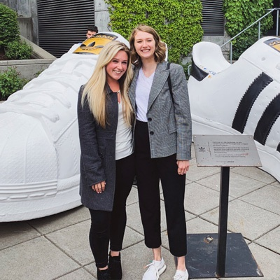 Two Warsaw Sports Business Club members pose for a photo next to two giant adidas shoes