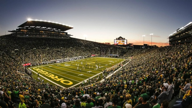 Photo of crowded Autzen stadium at night during a football game, looking west toward scoreboard