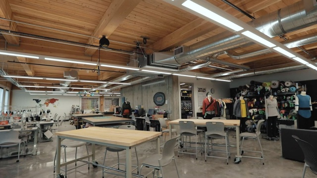 The SPM Innovation Lab is a wide open collabrative space with wood ceitling and beams, ample work tables, sewing equipment, fabric, and inspiration.