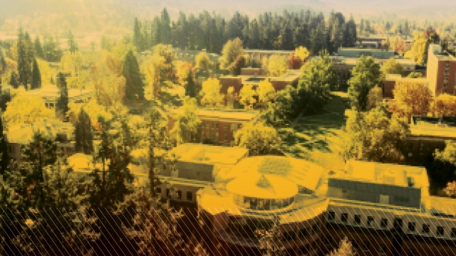 Oblique aerial photograph of the Lillis Business Complex from the north side looking south over the campus and hills of Eugene with a bright green sunny overlay on the photo