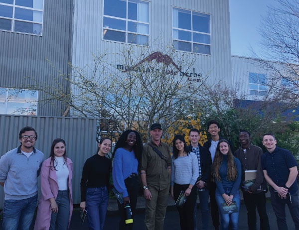 Members of the Net Impact group post for a group photo together outside of Mountain Rose Herbs headquarters in Eugene, Oregon