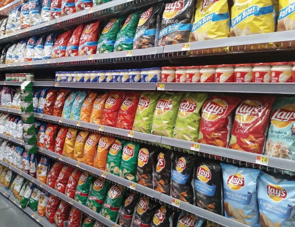 Rows of different brands of potato chips in a supermarket aisle