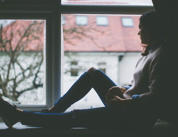 A woman sits on a window sill on a rainy day and looks outside