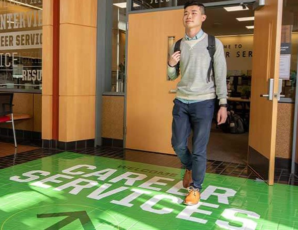 A student walks out of Mohr Career Services into the Lillis atrium