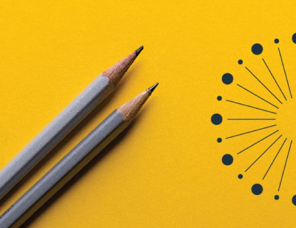 Two pencils sit on a yellow surface