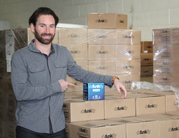Defunkify Chief Marketing Officer Eddie Rosenberg poses beside a palette of the product
