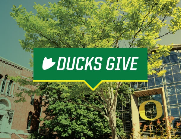 DucksGive logo against a background image of the Lillis Business Complex