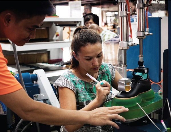 A student uses a shoe-making machine