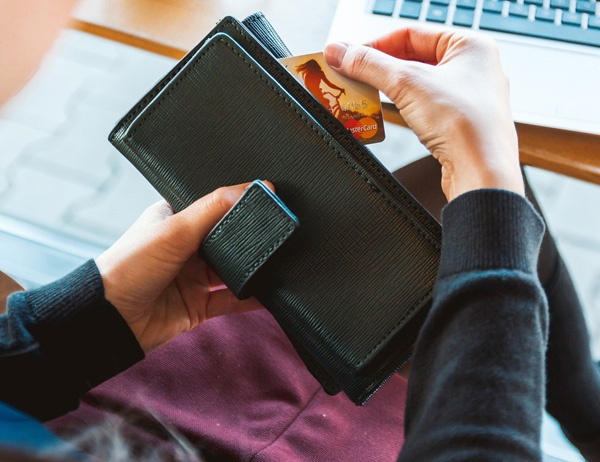 A person pulls a credit card out of their wallet