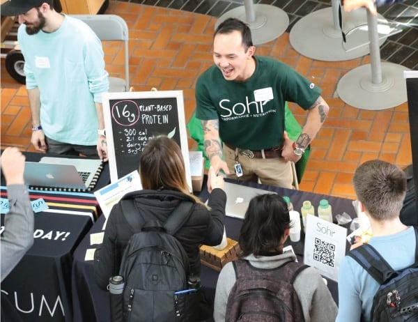 An Oregon MBA alumnus greets students while tabling at the Business Careers in Food and Beverage event