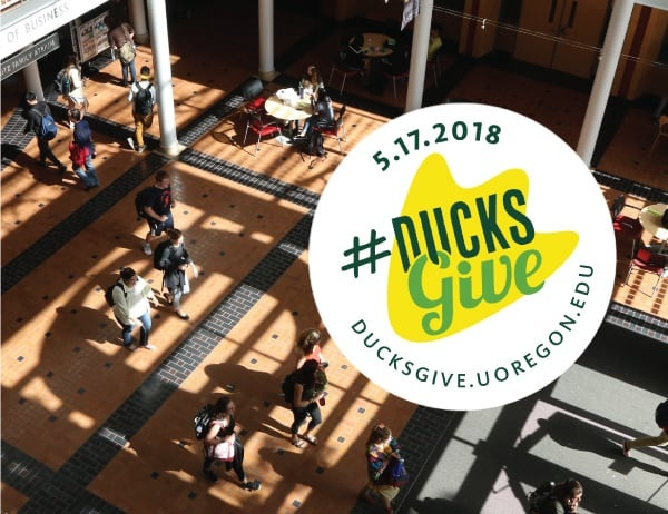 Ducks Give logo against a background of the Lillis atrium