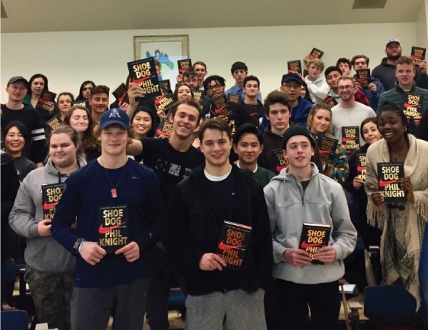 Students pose holding Phil Knight's Shoe Dog book