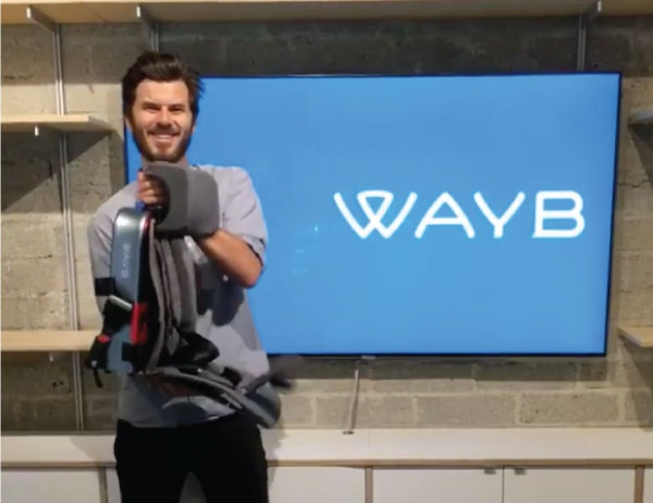 MBA intern poses in WayB headquarters with child's car seat