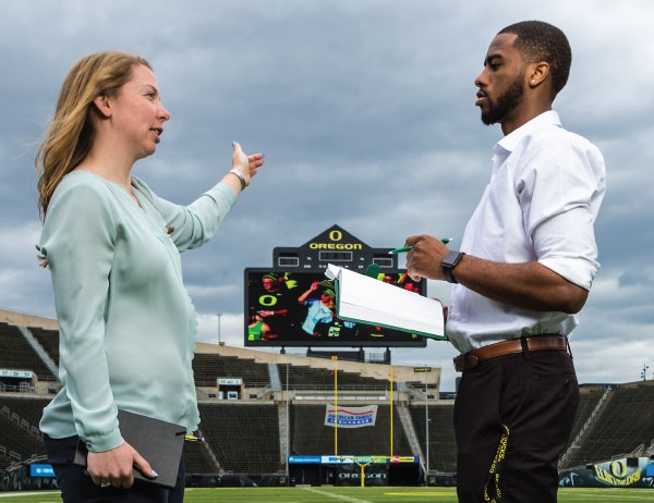 Two students talk on the field of a sports arena