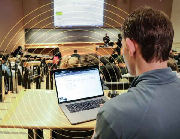 A student takes notes on his laptop during class in a large auditorium