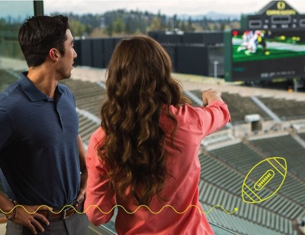 Two young people look out over a football field.