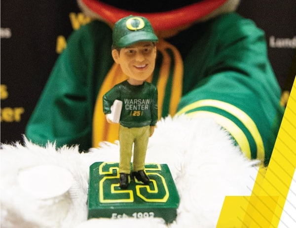 The Oregon Duck mascot holds the Jim Warsaw bobblehead commemorating the Warsaw Center's 25th anniversary