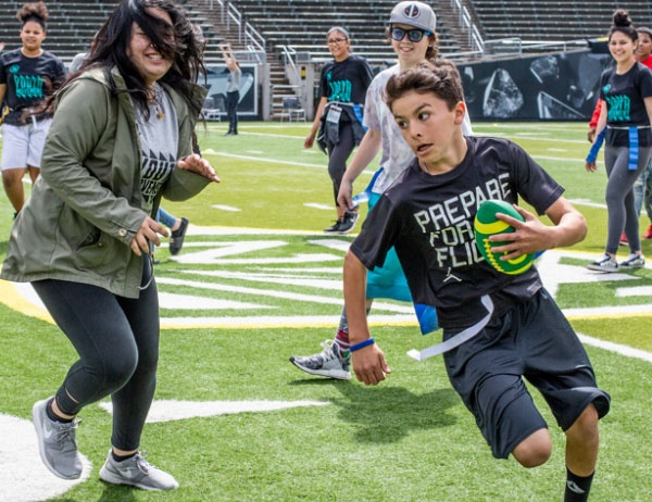 Children play field games on Autzen Stadium