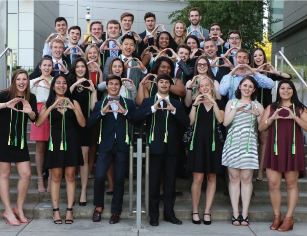 """A group of business honors students make the Oregon """"O"""" sign"""