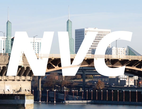 The letters NVC in white against a background of the Portland city skyline