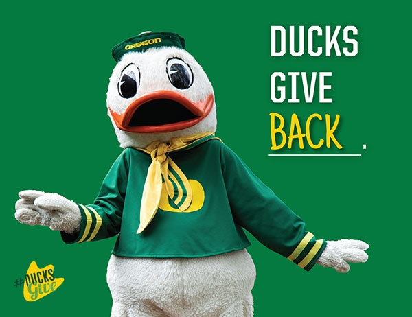 """Photo of the UO Duck next to the words """"Ducks Give Back"""""""