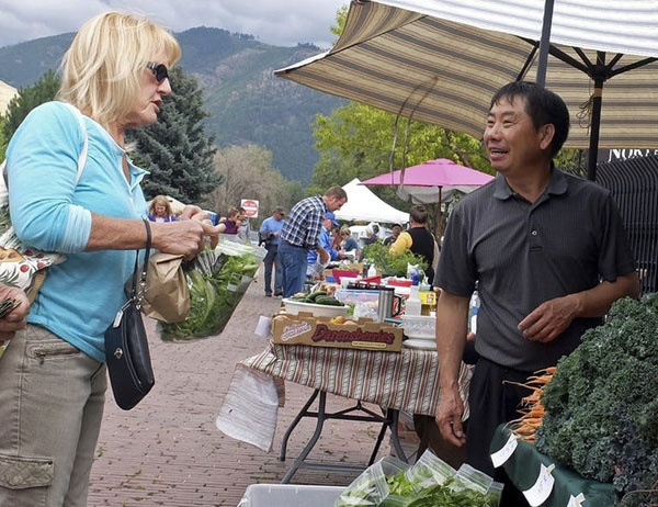 People look at vegetables at a farmer's market